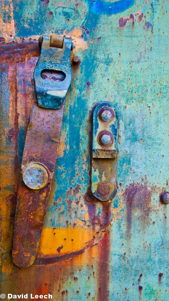 Armoured iron door latches, frozen in time, fading and rusting away.